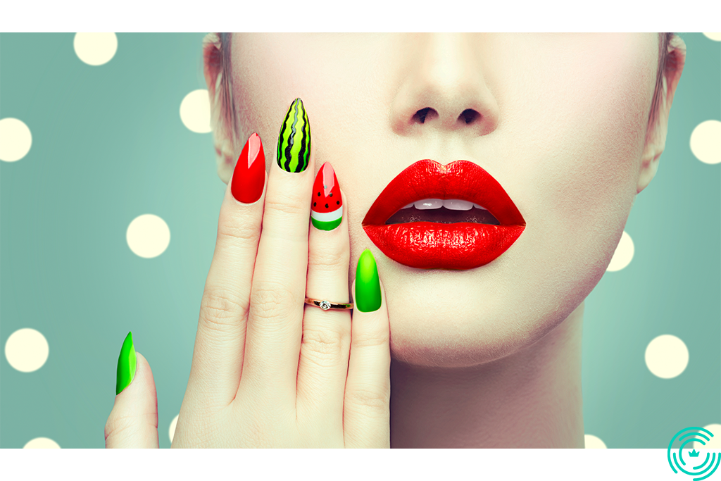The face of a woman and her hand with a manicure in shades of red and green