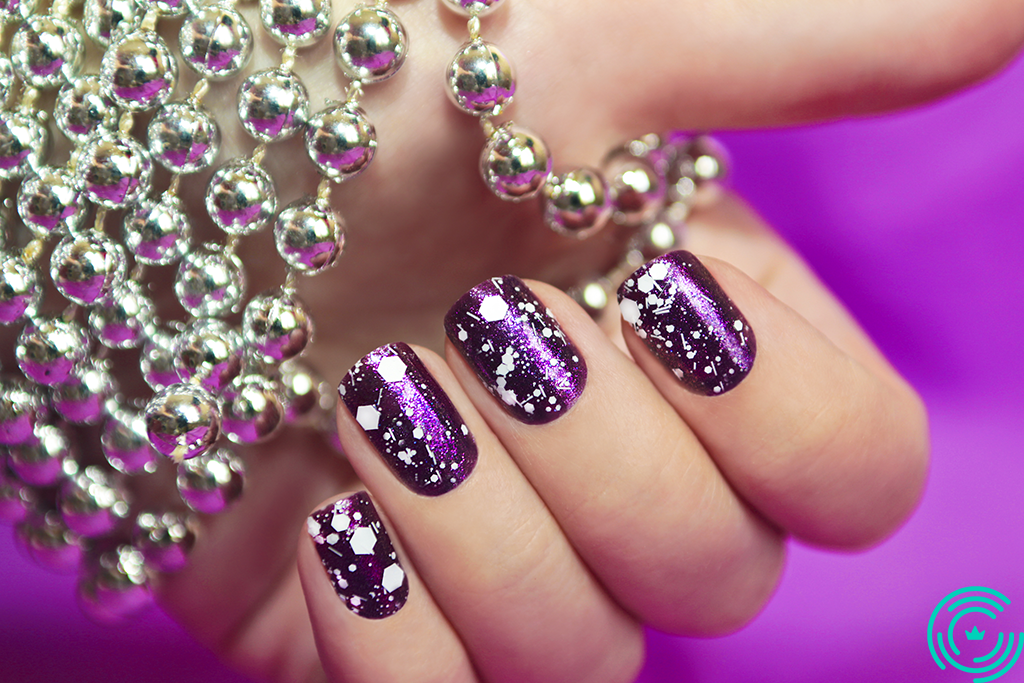 Woman's hand with glossy purple right manicure