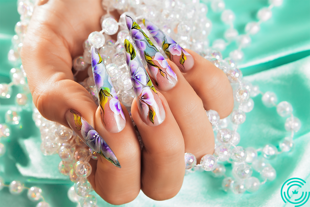 Woman's hand with very long and sharp nails and floral pattern applied on them