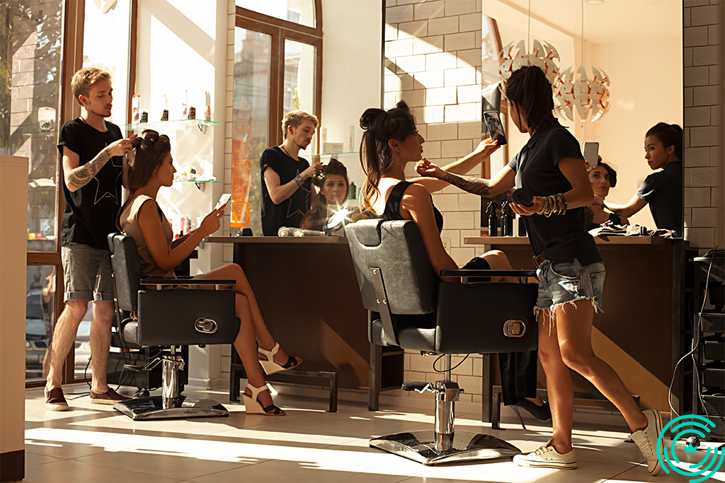 2 hairdressers (a man and a woman) in a salon with 2 female clients